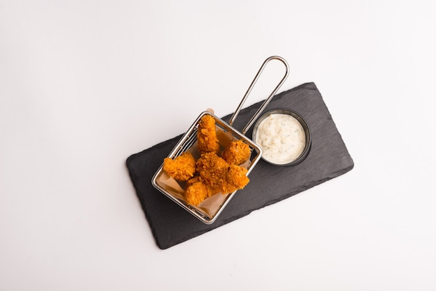 Very top view of a basket full of fried fingers or nuggets over white background.