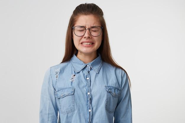 目を閉じて立っている眼鏡をかけた非常に動揺した若い女性が、口を開けて歯を食いしばって泣きました