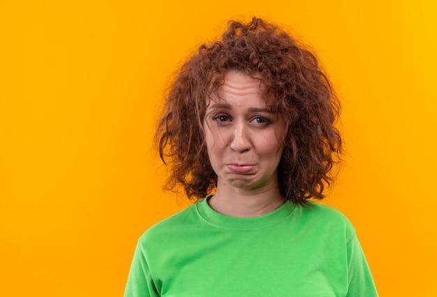 カメラのしかめっ面を見て緑のtシャツの短い巻き毛を持つ非常に動揺した若い女性