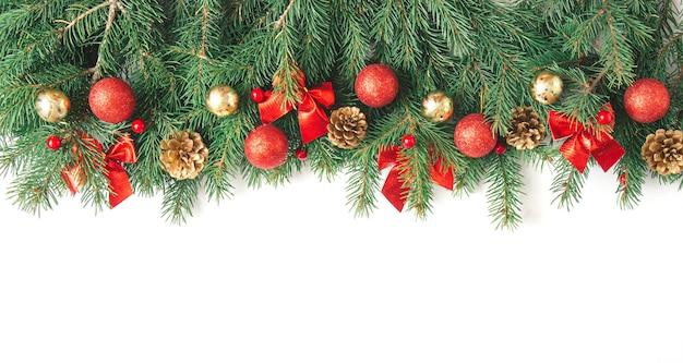 緑のモミの枝、弓、赤と金のクリスマスボール、白い背景で隔離のベリーと非常に広い冬のクリスマスの花輪のボーダーバナー。