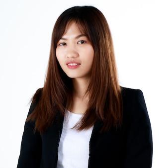 공식적인 검은 양복을 입은 아주 젊은 10대 여성 사업가가 귀엽고 자신감 있는 미소로 현대 사무실에서 직장 생활을 시작합니다. 새로 졸업한 학생들과 취업 첫 날을 위한 개념.