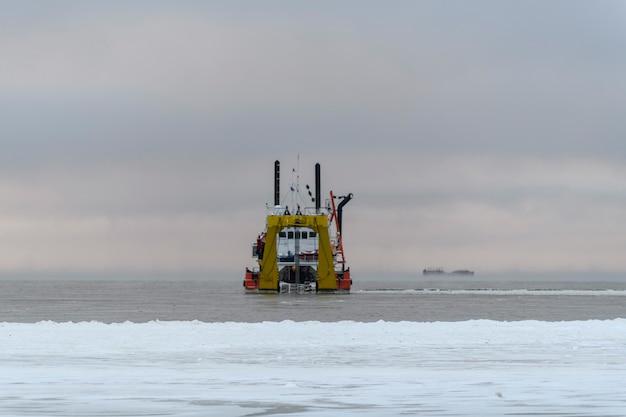Судно занято дноуглубительными работами во время заката. земснаряд с бункером, работающий в море. корабль выкапывает материал из водной среды.