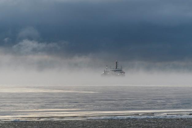 Судно занято дноуглубительными работами земснаряд работает в море сильный туман в арктическом море