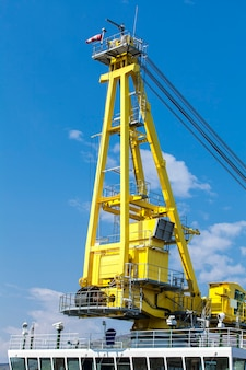 Vessel with a crane on a surface of blue sky in kamchatka