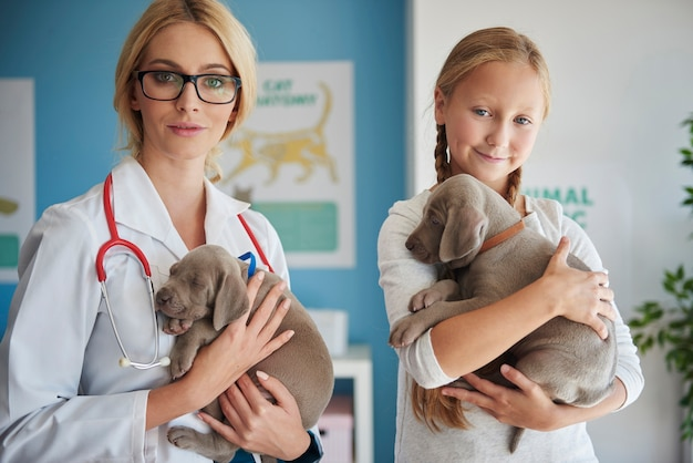 작은 강아지와 함께 포즈를 취하는 수 의사와 소녀