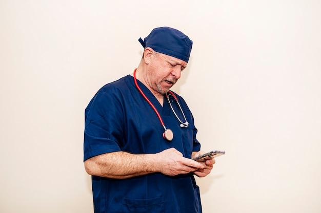 ベージュの壁とスマートフォンを使用してベテラン医師