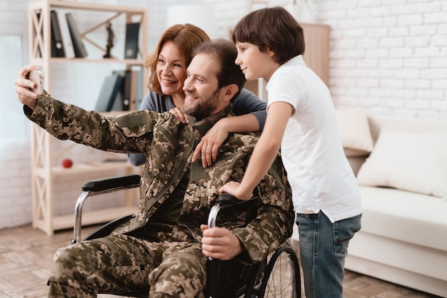 A veteran in a wheelchair makes selfie with his family.
