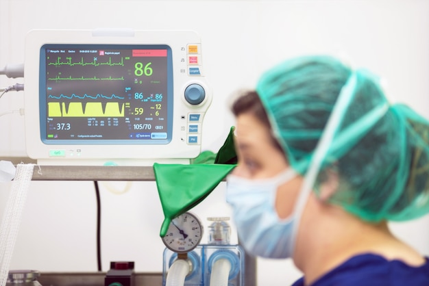 Veterinarian doctor portrait in operating room. anesthesia monitoring in the background