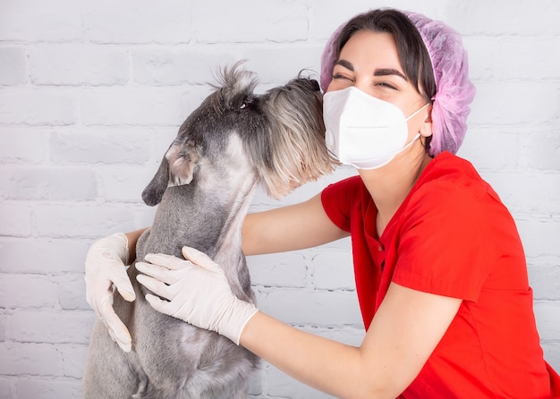 A veterinarian in a protective mask with a sdog