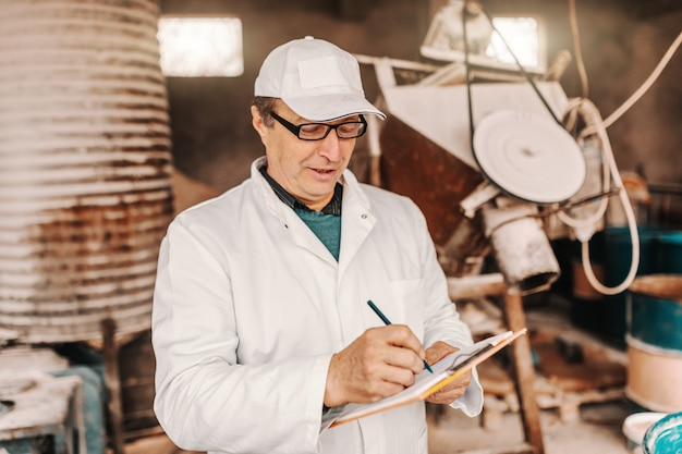 Veterinarian with cap, white uniform and eyeglasses writing results of animal examination while standing in the barn.