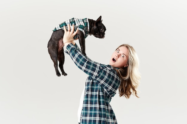 Ветеринарная концепция. счастливая женщина битника играя с французским бульдогом на белой стене