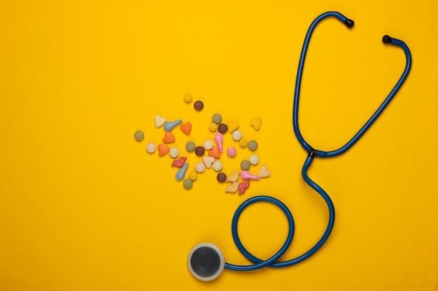 獣医の静物。動物の治療の概念。黄色の猫のためのビタミン剤と聴診器