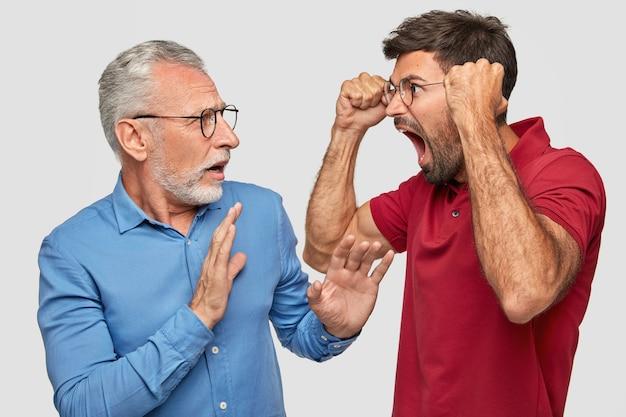 Раздраженный, раздраженный отец и молодой взрослый сын позируют у белой стены
