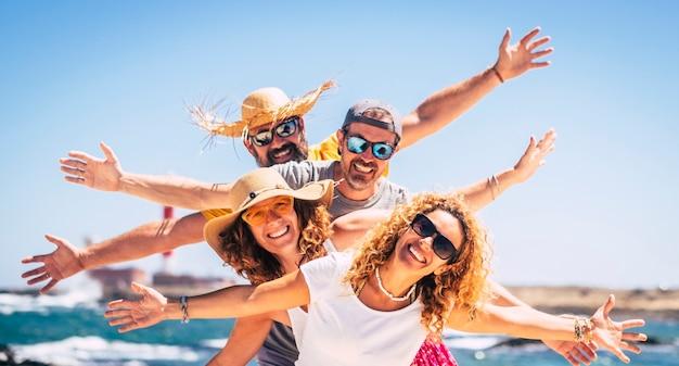 幸せな大人の友人のvgroupは、夏休み休暇旅行レジャー活動を一緒に楽しんで祝います-男性と女性が笑顔でバックグラウンドで海を楽しんでいます-楽しいカップル Premium写真