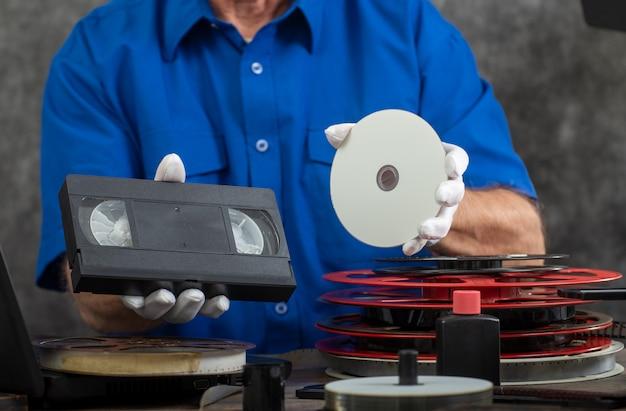変換用のvhsテープとdvdディスクを保持しているハンドカメラマン