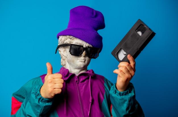 Античная статуя, одетая в модную одежду девяностых, держит кассету vhs