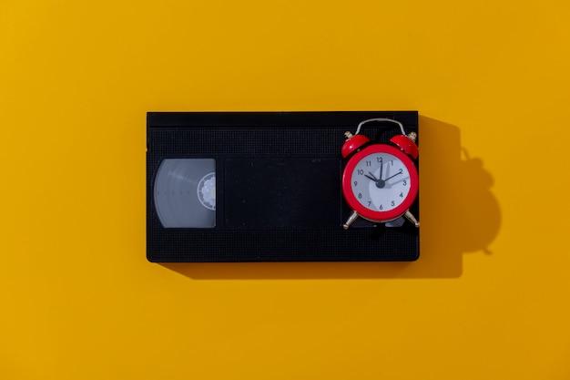黄色の背景に赤い目覚まし時計とvhsカセット