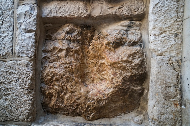 Via dolorosa, jerusalem, israel. an old square stone with a cavity which is said to be the imprint of jesus hand. jerusalem sightseeings. the track left by christ on stone wall while carrying cross.