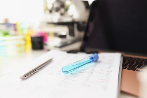 파란색 액체 유리병은 실험실에서 액체 연구를 수행하는 테스트 결과 문서에 있습니다.