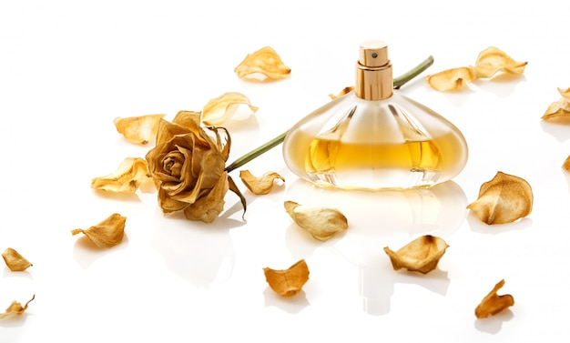 Vial of perfume and dry rose flower