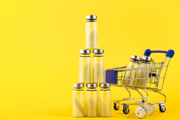 Флаконы, ампулы с сухим пробиотиком, бифидобактериями, с пробиотическим порошком внутри, на тележке в супермаркете. на желтом фоне.