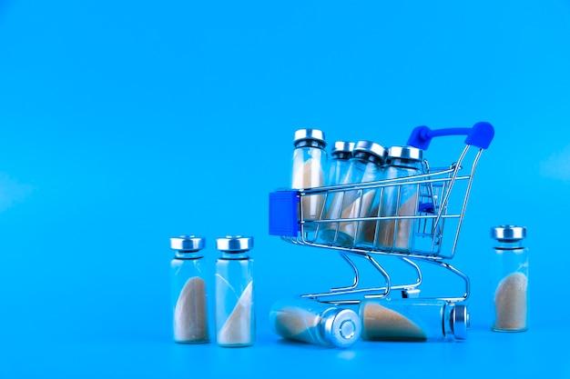Флаконы, ампулы с сухим пробиотиком, бифидобактериями, с пробиотическим порошком внутри, на тележке в супермаркете. на синем фоне. скопируйте пространство.