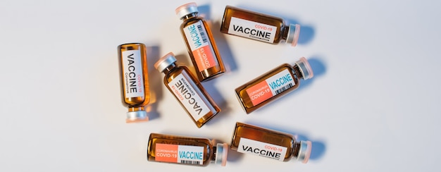 Vials of different coronavirus vaccine lie randomly on white background, close-up. covid-19 banner with copy space. completion of development of antiviral drug, mass vaccination of population.