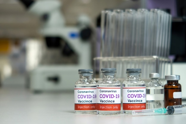 Covid-19コロナウイルスワクチンのバイアルと実験室の注射器と試験管。医学