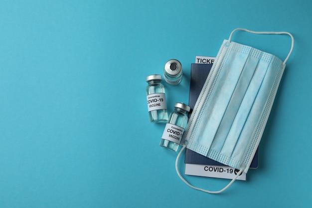 Covidのバイアル-19ワクチン、医療用マスク、青いテーブルのパスポート
