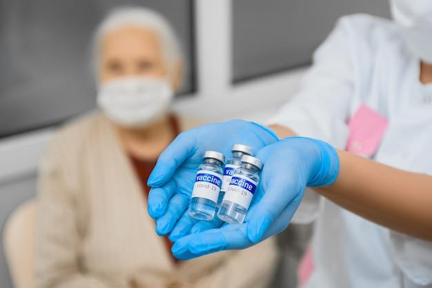 Флаконы с вакциной covid в руках врача на фоне пожилой женщины