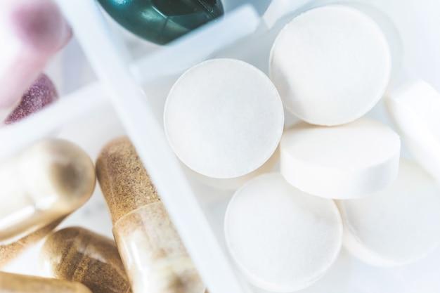 Взгляд сверху таблетки органической медицины альтернативной медицины или дополнения viatmin капсулы на предпосылке случая пилюльки. концепция здорового питания.
