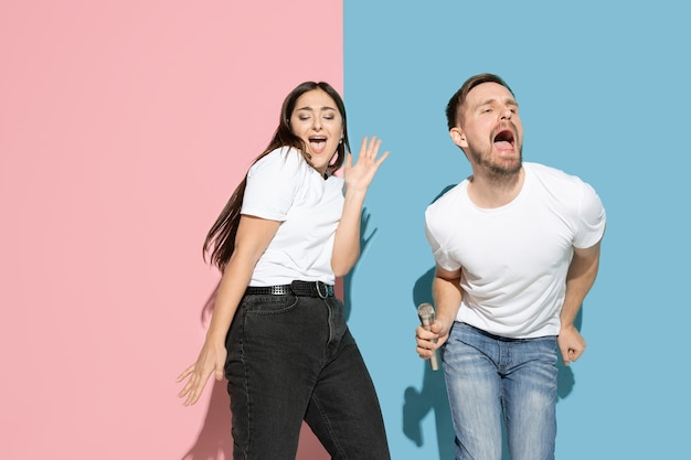 Vibes. dancing, singing, having fun. young and happy man and woman in casual clothes on pink, blue bicolored wall. concept of human emotions, facial expession, relations, ad. beautiful couple.
