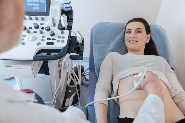 그녀의 장기를 검사하기 위해 초음파 장비를 사용하는 전문가 동안 침대에 누워 활기찬 매력적인 멋진 아가씨