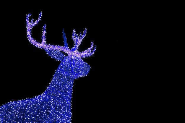 Яркие синие освещенные рождественские олени в форме уличных украшений на темном фоне