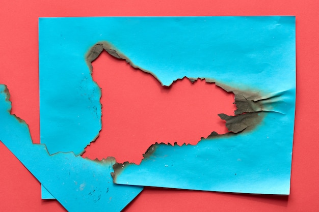 中央に焦げた穴のある鮮やかな色の紙の背景