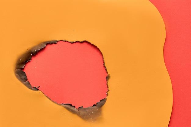 真ん中に焦げた穴のある鮮やかな色の紙の背景