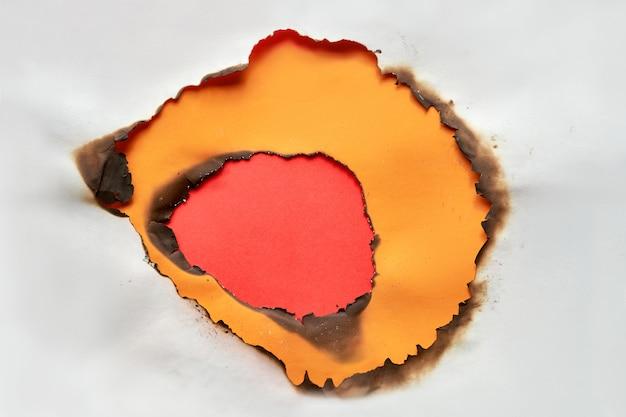 中央に焦げた穴のある鮮やかな色の紙の背景。