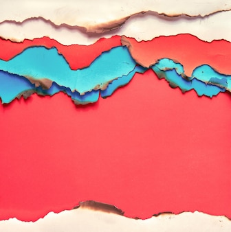 Vibrant color paper with burned edges, flat lay with copy-space
