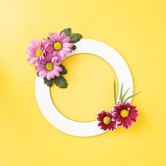 Яркие весенние цветущие цветы, расположенные в форме цикла с копией пространства на освещающем желтом фоне. минимальная творческая концепция.