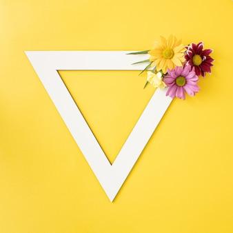 Яркие весенние цветущие цветы расположены в форме треугольника с копией пространства на желтом ярко-желтом фоне. минимальная творческая концепция.