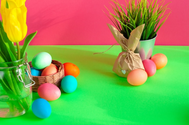 Vibrant colored eggs in a nest on green. easter concept