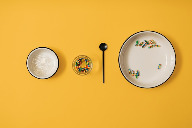 노란색 배경에 설탕 사탕 뿌리로 가득 찬 약 캡슐의 생동감 있는 다채로운 평면 누워. 약물 과다 복용과 식품 보충제 중독에 대한 창의적인 개념.