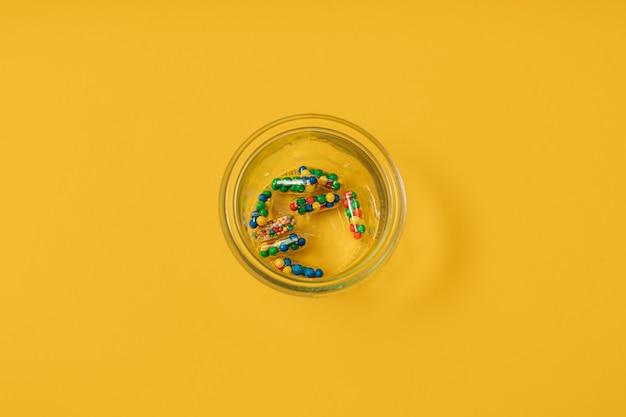 黄色の背景に砂糖菓子をまぶした薬の丸薬カプセルの鮮やかなカラフルなフラットレイ。過剰摂取の薬の使用と栄養補助食品への依存症の創造的な概念。