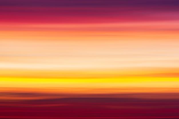 흐릿한 일몰 하늘에 붉은 분홍색 보라색과 주황색 구름의 생생한 다채로운 줄무늬 배경