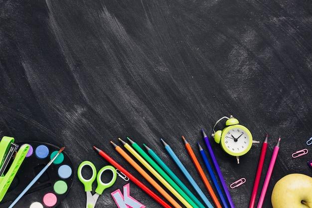 Vibrant creative stationery at bottom on grey background