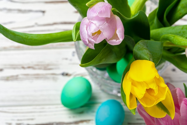 Vibrant easter eggs with flowers in a glass jar close up, cropped image