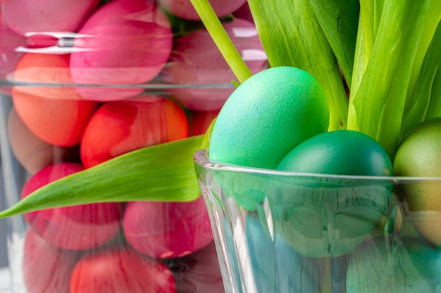 Vibrant easter eggs with flowers in a glass jar