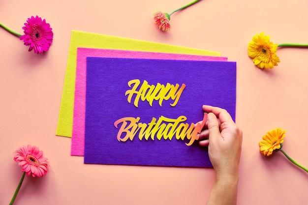 Яркая квартира с цветами герберы и ромашками и фетром с бумажным текстом «с днем рождения» в руке на коралловой бумаге.