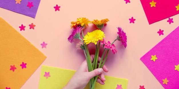Яркая квартира, лежащая на бумаге с геометрическими фигурами, рука держит три цветка герберы