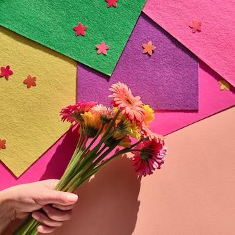 幾何学的な紙の上に3つのガーベラの花を持っている手で活気に満ちたフラットレイ